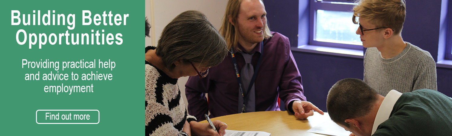Providing practical help and advise to achieve employment, BBO team with clients sat around a desk talking.